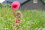Little girl with hat in wild daisy field.