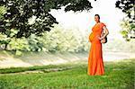 belle jeune heureuse femme enceinte en plein air dans la nature brillante en robe orange