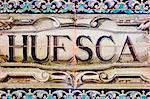 a Huesca sign writen in mosaic tiles