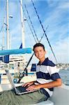 boy teenager seat on boat marina laptop computer summer vacation