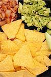 Nacho tortilla chips with dips and avocado