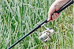 Closeup of a fisherwoman hand holding a fishing rod