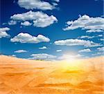 sandy desert with the rising sun on the horizon