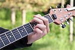 A closeup shot of a young man playing his guitar.