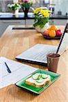 Sandwich, document papier et ordinateur portable sur la table de la cuisine