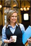 Portrait de femme d'affaires Mid holding café file et takaway