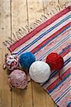 Pelotes de laine et des tapis tricotés sur plancher en bois
