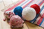 Gros - plan vue de pelotes de laine et des tapis tricotés sur plancher en bois