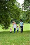 Parents walking with children in park
