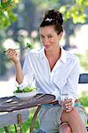Beautiful brunette eating salad in the garden