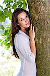 Beautiful brunette girl leaning against tree