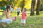 Petite fille et femme soufflant des bulles dans le parc