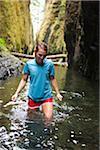 Frau Wandern durch Fluss, Oneonta Schlucht, Oregon, USA