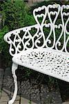 White wrought iron bench in a garden