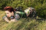 Attractive tattooed Caucasianwoman in camouflage lying on grass looking through binoculars in Maui, Hawaii, USA.