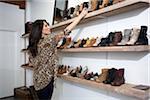 Shop Owner Arranging Shoes on Shelf