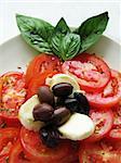 close up photo of italian caprese tomato mozzarella olive salad