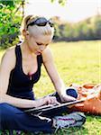 Une femme dans le sport vêtements assis dans l'herbe en utilisant une tablette numérique