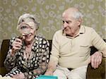 Homme Senior amusé comme femme senior amplifie l'apparence de le œil avec loupe