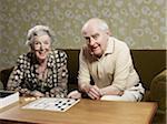 Femme et homme senior jouent muehle sur canapé