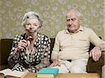 Senior homme fronce les sourcils comme femme senior amplifie l'apparence de sa bouche avec loupe