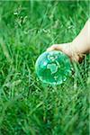 Main de l'enfant avec des boules de verre sur l'herbe.