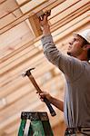 Hispanic carpenter hammering metal reinforcement bracing at a house under construction