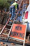 Cable installer climbing a ladder near a Men at Work sign