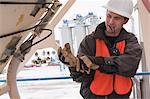 Engineer putting on work gloves on tank tower inspection platform