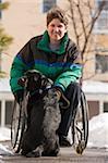 Frau mit multipler Sklerose spielen mit einem Dienst-Hund im winter