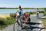 Famille multigénérationnelle bénéficiant d'enfants assis dans la remorque pour vélo, balade à vélo