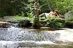 Jeune femme reposante sur la roche de flux de fluide