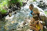 Famille ensemble accroupi à côté des cours d'eau, en regardant l'eau