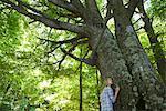 Jeune femme appuyé contre l'arbre, en levant