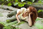 Jeune femme reposante sur la roche