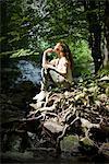 Jeune femme assise de flux dans les bois