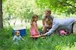 Famille ayant un pique-nique dans la prairie