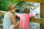 Girl and baby sister looking over railing of bridge at stream below