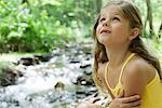 Girl beside stream, looking up in awe