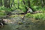 Jeune femme assise de rivière traversant les bois