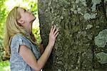 Jeune femme regardant vers le haut arbre