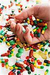 Man's hand full of pills and capsules
