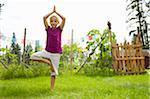 Girl doing yoga in backyard.