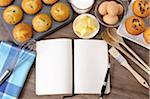 Livre de cuisine vide avec muffins frais et ingrédients