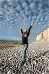 Étirage de la femme sur la plage à main levée