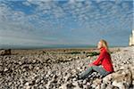 Femme assise sur la plage avec les yeux fermés