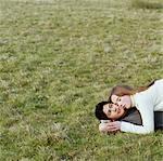 Teenage couple (15-17) lying on grass