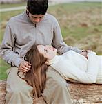 Teenage couple (15-17) on log, girl resting head on boys lap