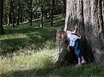 Girl (6-8) peering around tree, rear view