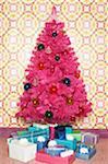 Gefälschte Rosa Weihnachtsbaum umgeben von Geschenken